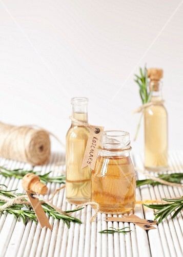 Small bottles of rosemary syrup with fresh rosemary sprigs