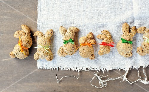 Crispy bread rabbits made from spelt dough decorated with bows for Easter