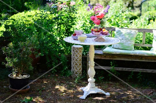 Round vintage-style garden table and wooden bench in summery garden