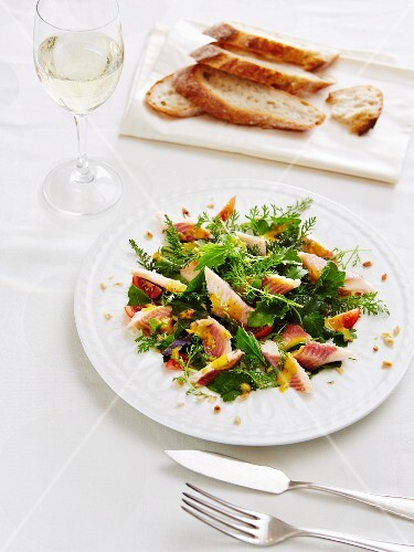 Smoked trout with a wild herb salad and bread served with a glass of white wine