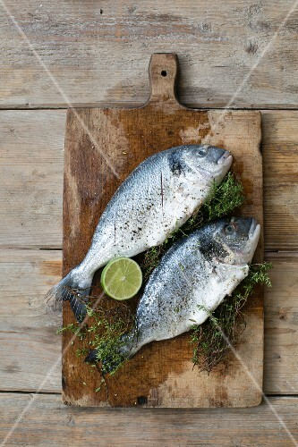 Seabream with herbs and lime on a chopping board