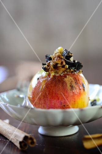 A baked apple filled with dried plums and walnuts