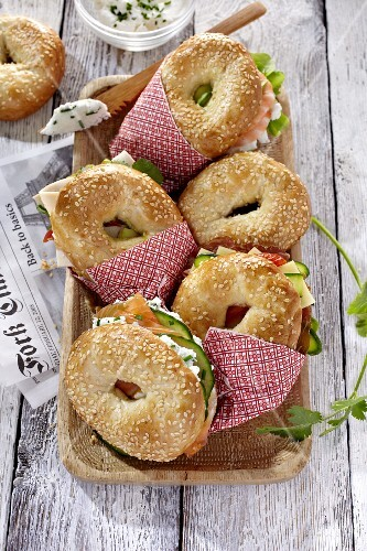 Various bagel sandwiches in a wooden dish
