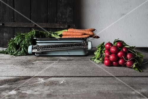 A bundle of carrots on an old pair of scales and a bundle of radishes