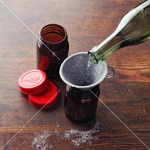 Vine ash dental wine à la Hildegard von Bingen being poured into a bottle