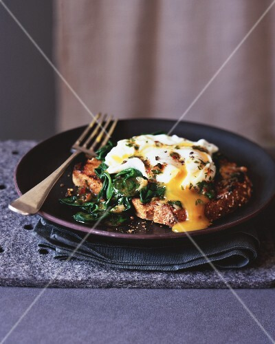 A poached egg wit spinach on toast