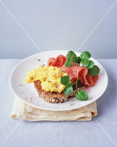 Wholemeal bread topped with scrambled eggs, smoked salmon and water cress