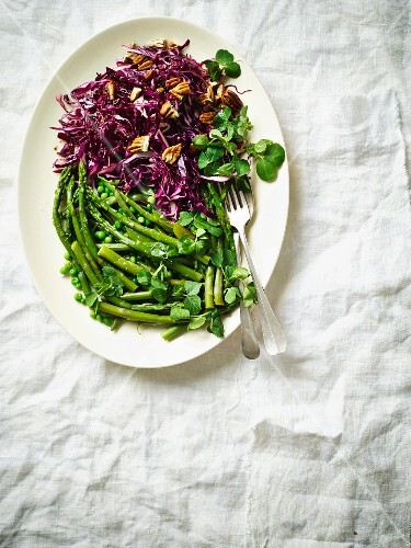 Green vegetables with clover and a red cabbage salad with pecan nuts for St. Patrick's Day