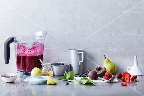 An arrangement of smoothie ingredients and a red smoothie in a blender