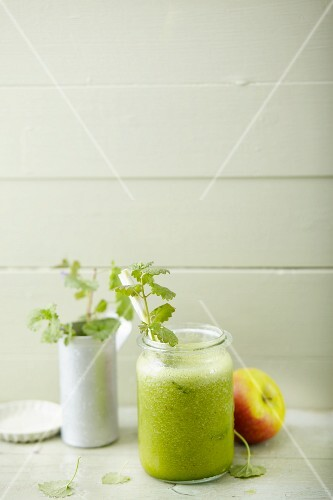 An orange and apple smoothie with spinach and ground ivy