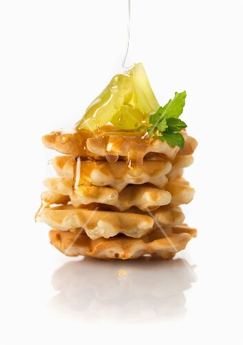 Syrup being poured over vegan waffles