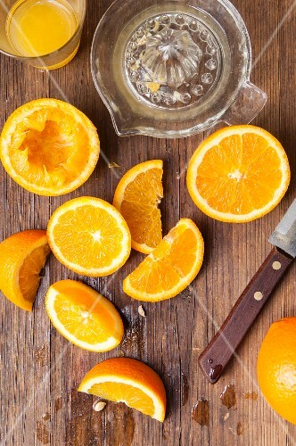 A glass of orange juice with a citrus press and juiced and sliced oranges
