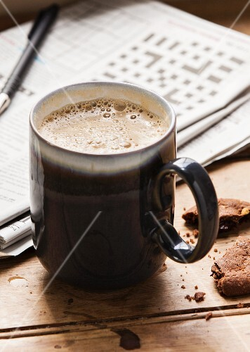 A cappuccino, a chocolate biscuit and a newspaper with a crossword on a wooden table