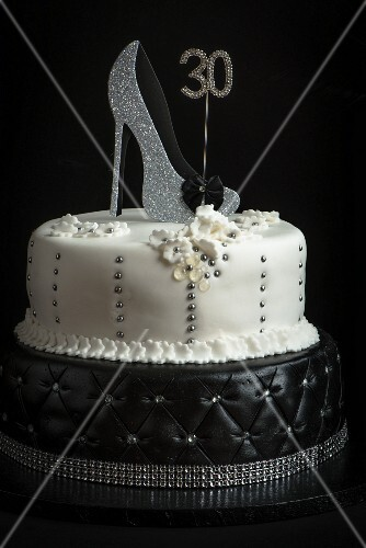 A two tier birthday cake in black and white decorated with a shoe