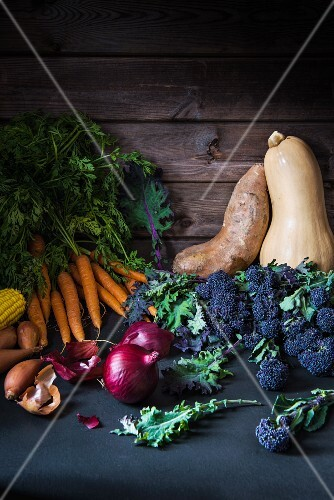 An arrangement of autumnal vegetables featuring squash, carrots, onions and broccoli