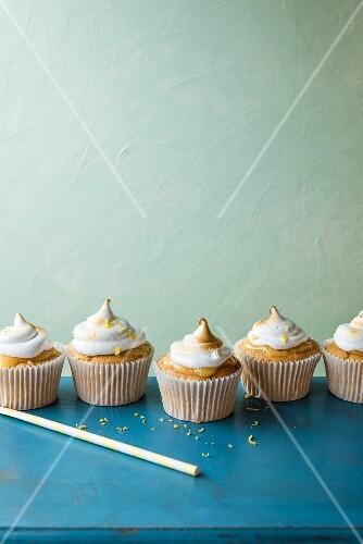 Lemon meringue cupcakes on a blue table