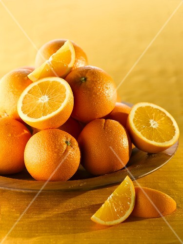 Oranges, whole and halved, in a wooden bowl