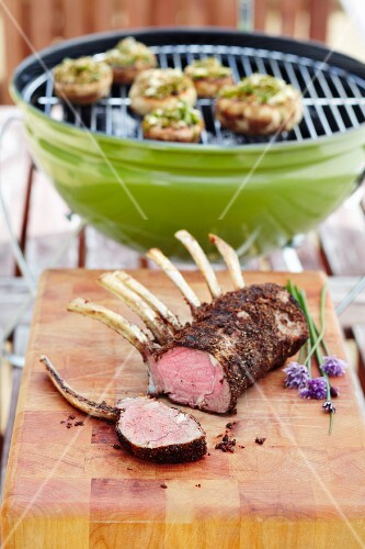 Grilled lamb rack with a barbecue in the background