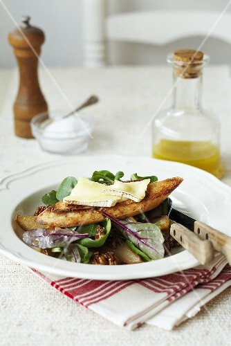 A mixed leaf salad with walnuts, toasted bread and brie