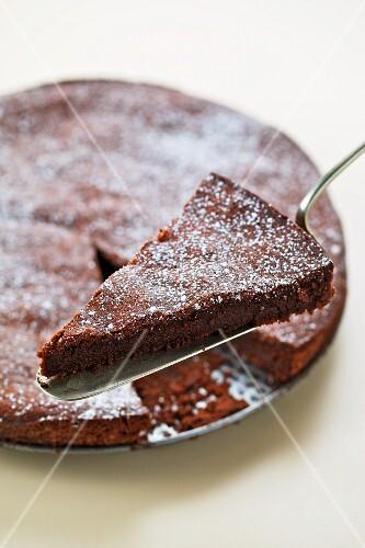 A chocolate cake with a piece on a cake slice