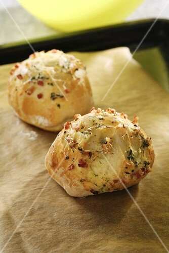 Freshly baked cheese rolls with bacon and herbs on a baking tray