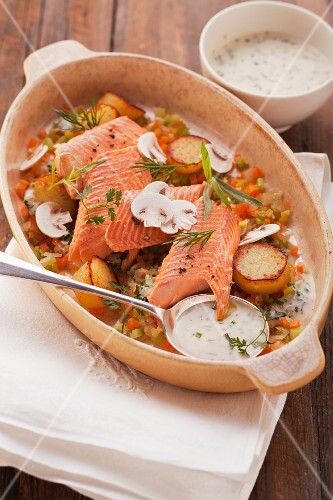 Brook trout with vegetables in a creamy white wine sauce