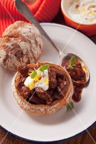 Beef goulash served in a hollowed out bread roll