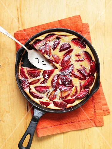 Clafoutis with plums in a pan