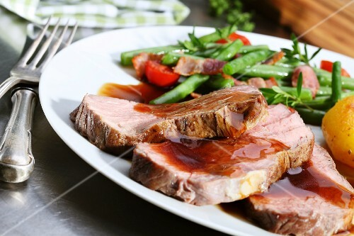 Roast beef with gravy and bacon beans