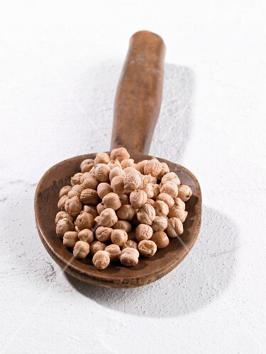 A pile of chickpeas on a wooden spoon