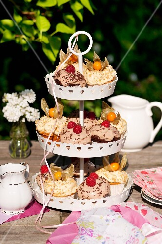 Various cupcakes on a cake stand on a garden table