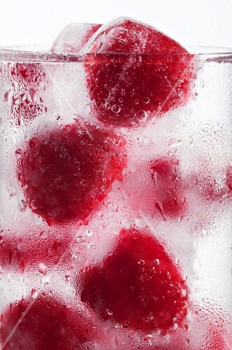 A glass of water with raspberry ice cubes