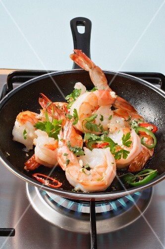 Prawns being mixed with herbs and chilis