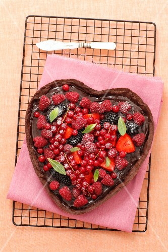 A heart-shaped chocolate cake decorated with berries