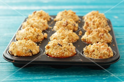 Apple muffins topped with nut crumble in a muffin tin