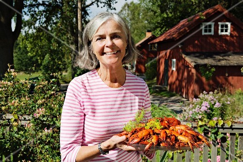 A woman serving a plate of crayfish (Sweden)
