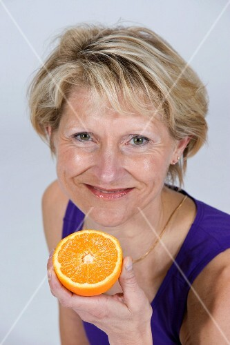A woman holding half an orange