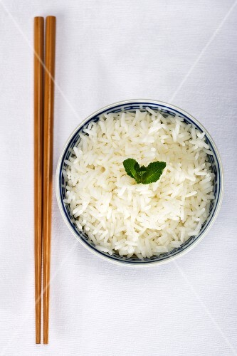 Chopsticks and a bowl of rice garnished with a mint leaf