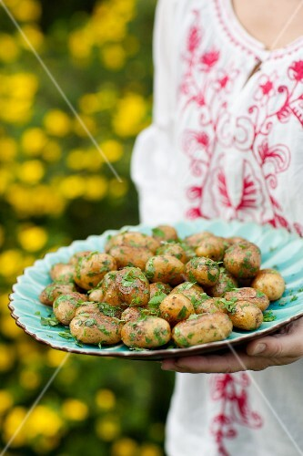 Woman holding plate with roasted herb potatoes