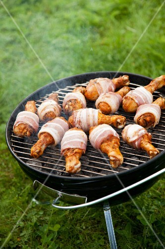 Bacon-wrapped chicken legs on barbecue