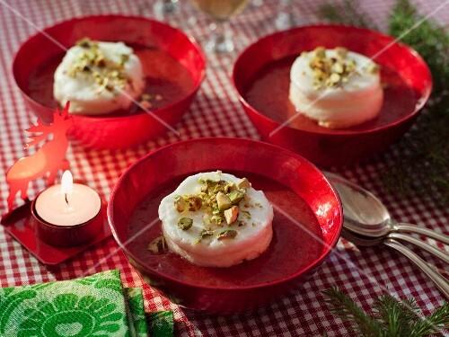 Vanilla dessert with pistachios on strawberry sauce