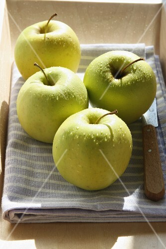 Apples on a tea towel with a knife