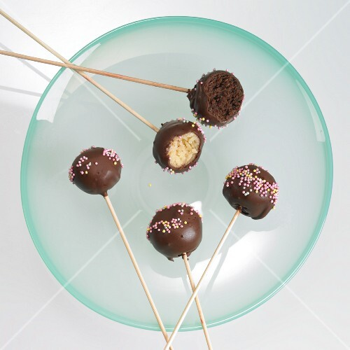 Cake pops with chocolate icing and sugar strands, one with a bite taken out