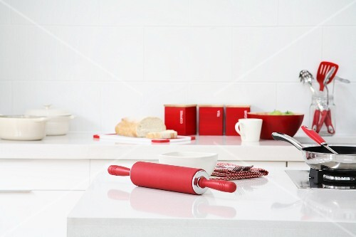Red silicon rolling pin on white worktop