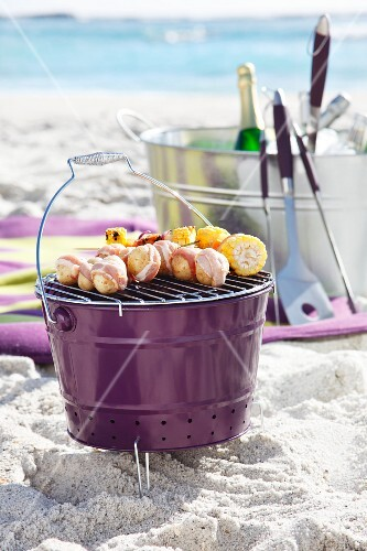 Bucket barbecue with skewers on sandy beach
