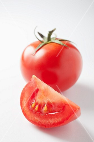 A slice of tomato and a whole tomato