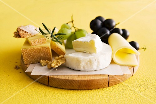 A cheese plater with grapes and nuts