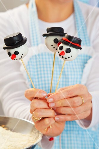 A woman holding snowman cake pops