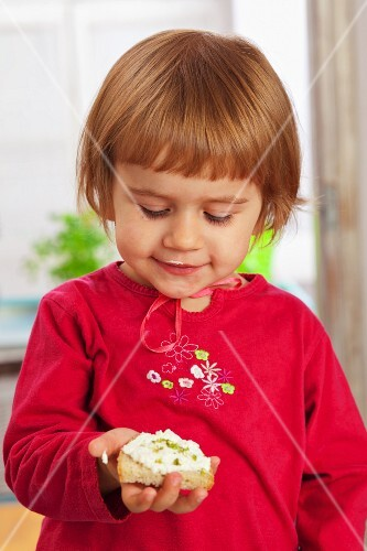 A little girl holding a slice of bread topped with cottage cheese