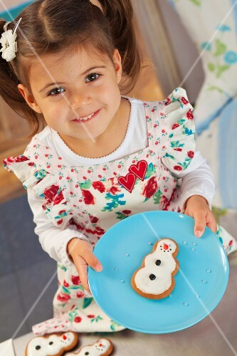 A little girl holding a gingerbread snowman on a plate